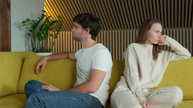 関係の問題を経験している若いカップルは、黄色いソファの上で家で隣同士に座っています