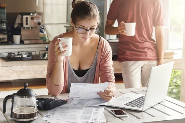 財政問題に直面し、キッチンで家計を管理する若いカップル。コーヒーを飲みながら一枚の紙を保持しているメガネのカジュアルな女性
