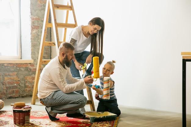 若いカップル、家族が一緒にアパートの修理をしています。母、父、息子が家のイメージチェンジやリフォームをしています。関係、移動、愛の概念。壁紙用の壁の準備