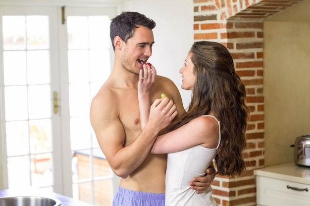 Young couple feeding fruits to each other in kitchen