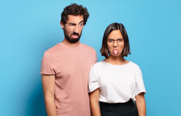 Молодая пара чувствует отвращение и раздражение, высовывает язык, не любит что-то противное и противное