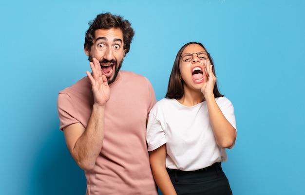 若いカップルは幸せ、興奮、前向きに感じ、口の横に手を置いて大きな叫び声を上げ、声をかけます