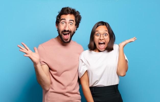 若いカップルは、信じられないほどの何かに幸せ、興奮、驚き、またはショックを受け、笑顔で驚いたと感じています