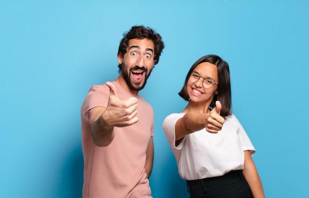 若いカップルは、誇りに思って、のんきで、自信を持って幸せに感じ、親指を立てて前向きに笑っています
