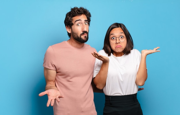 困惑して混乱している、疑っている、重み付けしている、または面白い表現でさまざまなオプションを選択している若いカップル
