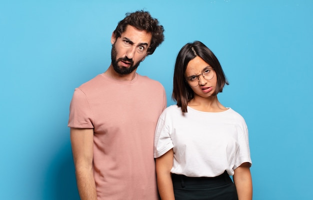 戸惑い、混乱している若いカップル、予想外の何かを見ている愚かな、唖然とした表情で