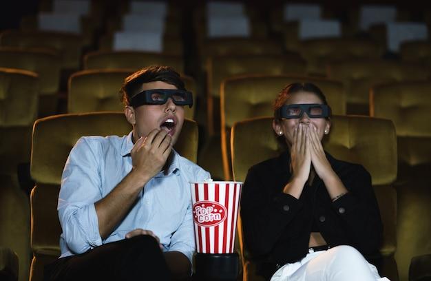 Молодая пара, чувствуя страх, поднимает руку, закрывает лицо во время просмотра 3d-фильма ужасов в кинотеатре