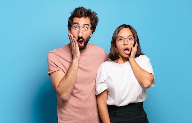 若いカップルはショックを受けて怖がって、口を開けて頬に手を当てて恐怖を感じています