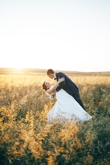 Young couple in the field of wheat in the sunset