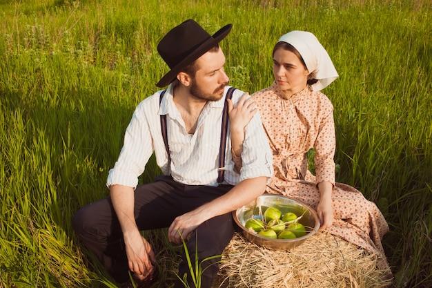 Giovani coppie nel campo con le mele