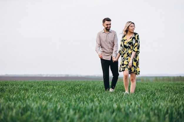 Young couple in the field with green grass