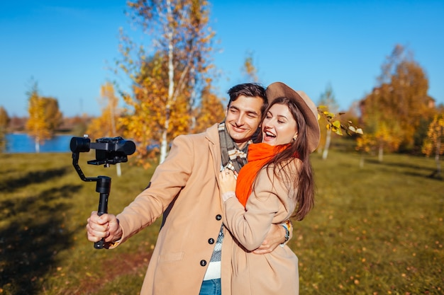 秋の森でステディカムを使用してビデオを撮影する若いカップル。屋外で楽しんでいる男性と女性のブロガー