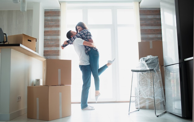 Young couple first time home owners celebrate moving day concept, man husband lifting holding wife standing near boxes in new own house apartment, relocation and family mortgage