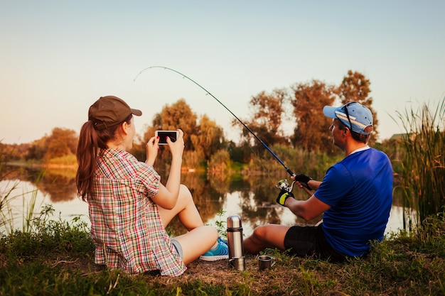 Young couple fishing and drinking tea on river at sunset