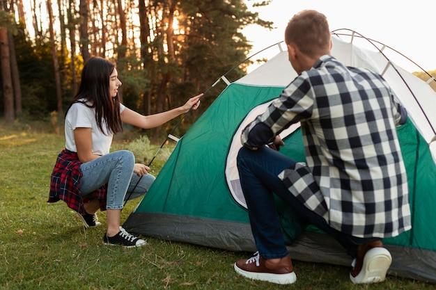 自然の中でテントを固定する若いカップル