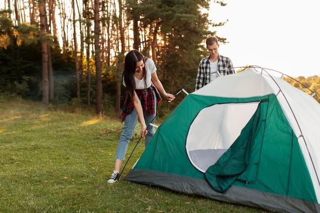 Giovani coppie che riparano tenda nella natura