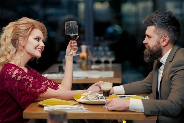 카페에서 유혹하는 젊은 부부는 와인을 마셔. 레스토랑에서 데이트하고 술을 마시는 아름다운 사람들. 결혼 생활