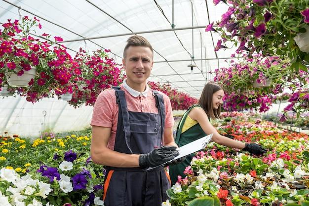 Молодая пара флористов, работающих с цветами и растениями в теплице