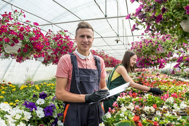 Young couple florists working with flowers and plants in the greenhouse