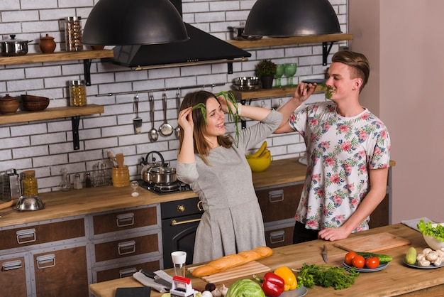 Young couple fooling with greenery in kitchen