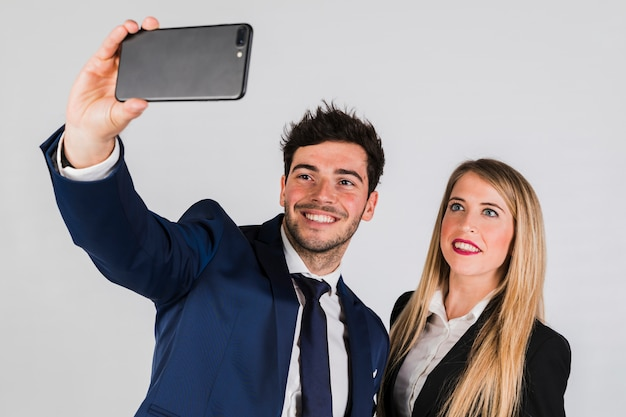 Young couple in formal wear taking selfie on smartphone on grey background