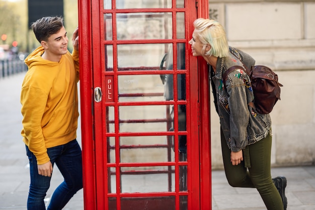 Young couple of friends near a classic british red phone booth