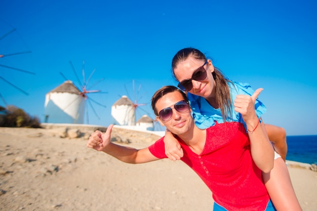 Young couple in front of windmills at popular tourist area on mykonos island, greece