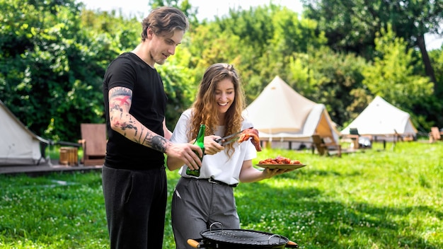 Young couple frying meat on the grill and drinking beer. greenery around. glamping