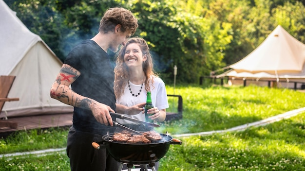 Young couple frying meat on the grill and drinking beer, laughing. greenery around. glamping