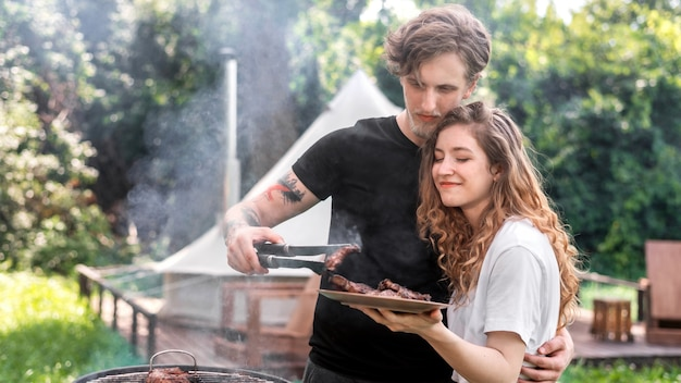 Young couple frying meat on the grill and putting it on the plate. greenery around. glamping
