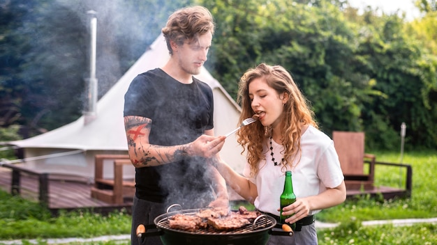 Young couple frying meat on the grill, trying it and drinking beer. greenery around. glamping