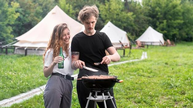 그릴에 고기를 튀기고 배경에서 맥주 텐트를 마시는 젊은 부부