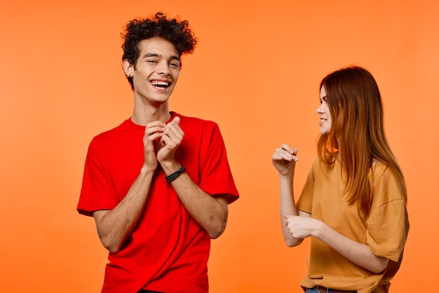 若いカップルの楽しい友情コミュニケーションオレンジ背景ファッション