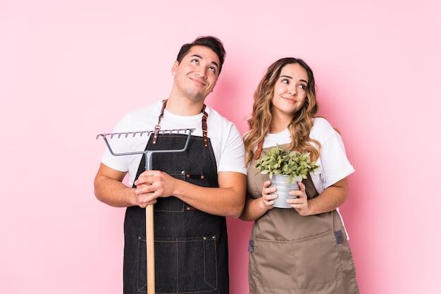 Молодая пара садовник изолированно мечтает о достижении целей и задач