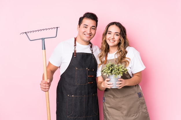 Young couple gardener isolated happy, smiling and cheerful.