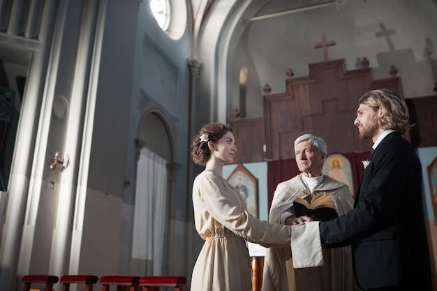 司祭が祈りを読んでいる間、教会で結婚する若いカップル