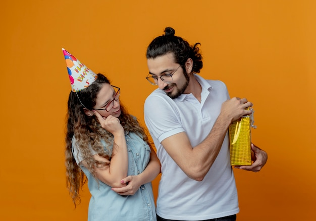 Young couple girl in birthday cap thinking and guy covered gift isolated on orange