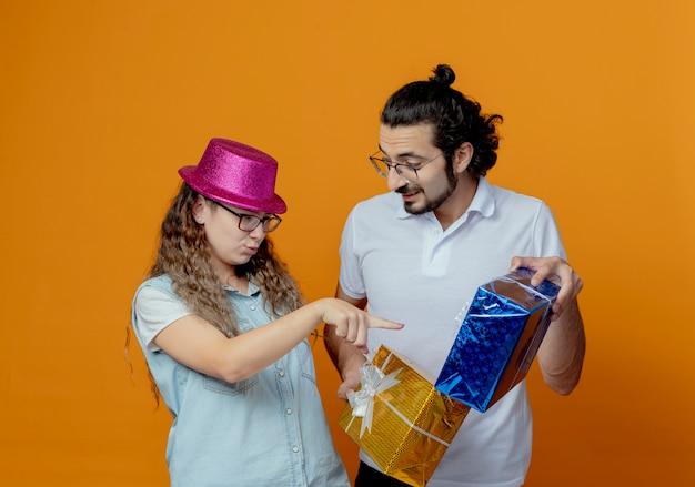 Молодая пара девушка в розовой шляпе указывает на подарок в руках парня, изолированного на оранжевой стене