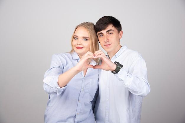 Giovani coppie della ragazza e del ragazzo che stanno insieme facendo la forma di simbolo del cuore con le mani.