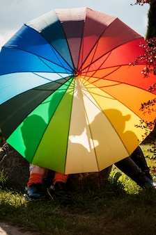 Young couple of girls. girls in love with lgbt umbrella. two kissing girls concept. silhouette of two girls in love.