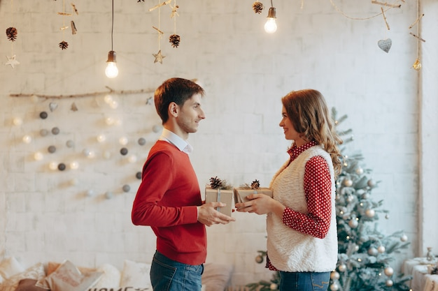 Young couple give christmas presents to each other
