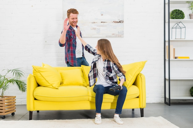 Young couple giving high five to each other after playing the video game
