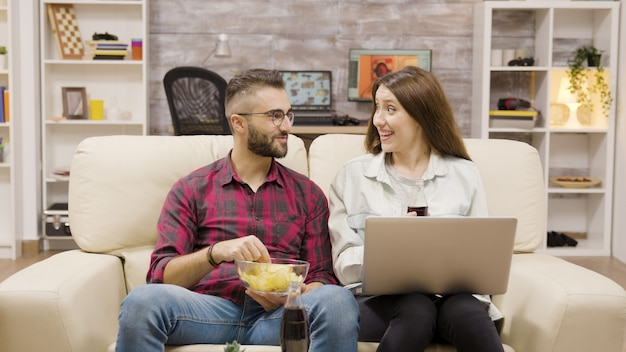 ソファに座ってハイタッチをする若いカップル。ソーダとチップを楽しむカップル。