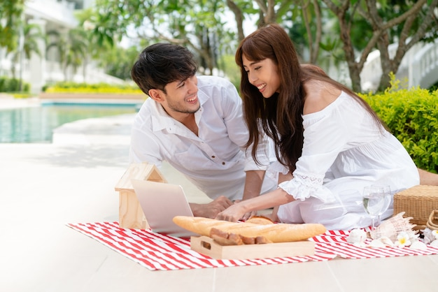 Young couple go picnic at the park in summer.