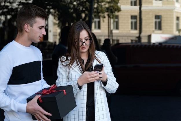 젊은 부부는 선물을 가지고 방문합니다. 남자는 선물 상자와 여자 휴대 전화를 보유하고 있습니다. 온라인 선물 주문.