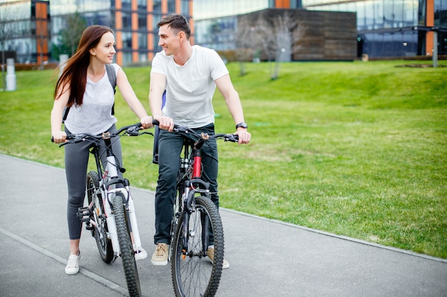Young couple going for a bike ride on a sunny day in the city