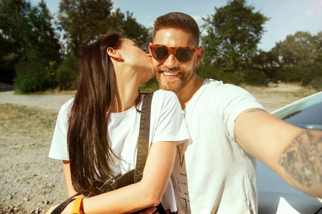 晴れた夏の日に車で休暇に行く若いカップル。森の中で自分撮りをしている女性と男性が幸せそうに見えます。関係、休暇、夏、休日、週末、新婚旅行の概念。