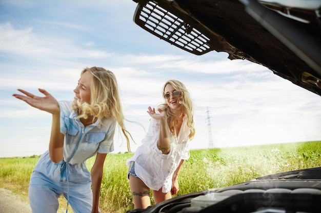 Young couple going to vacation trip on the car in sunny day