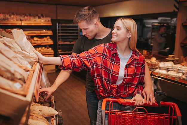 Young couple in grocery store picking up bread