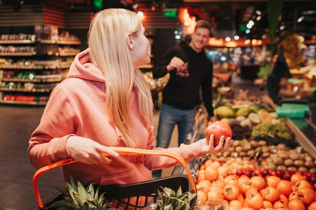 Young couple in grocery store taking fruits
